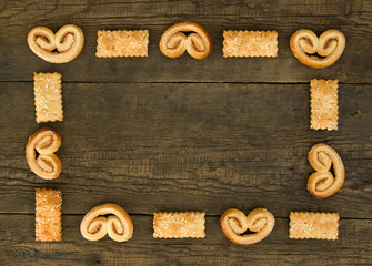 Frame from puff sweet pretzels with cinnamon  and cookies with  sesame on the wooden background
