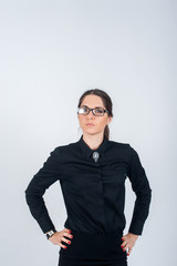 Serious girl with glasses standing in Studio on white background