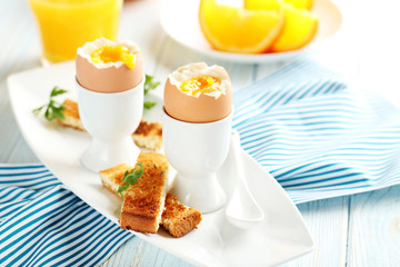 Boiled egg with toasts on a blue wooden table