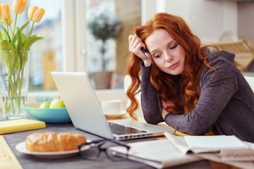 frau sitzt am küchentisch und schaut genervt auf ihren laptop