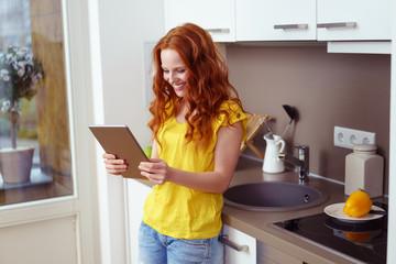 frau steht in der küche und sucht nach rezepten im internet