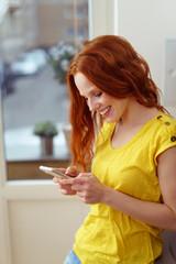 modernen junge frau in der wohnung tippt eine sms auf ihrem handy