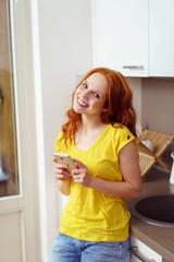 lachende frau steht in ihrer küche und hält ihr handy in den händen