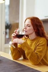 frau genießt ein glas rotwein in ihrer küche