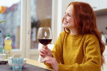 frau sitzt am küchentisch mit einem glas rotwein