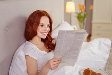 frau liegt morgens gemütlich im bett und liest die tageszeitung
