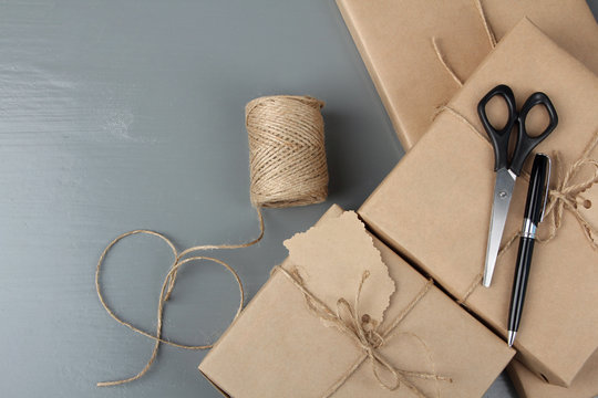 packages with tags and a ball of string and scissors on grey wooden background closeup