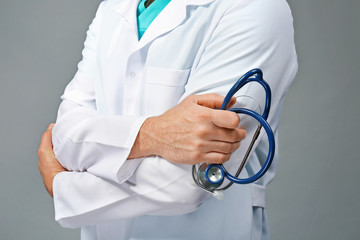 Doctor with crossed hands and stethoscope on grey background, close up