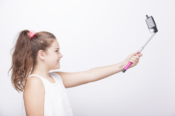 Little girl using a selfie stick on grey background