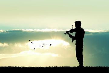 Man playing the violin at sunset