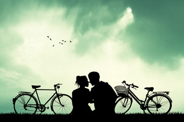 couple with bicycles at sunset