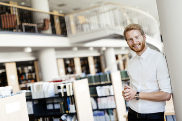 Handsome student smiling in library