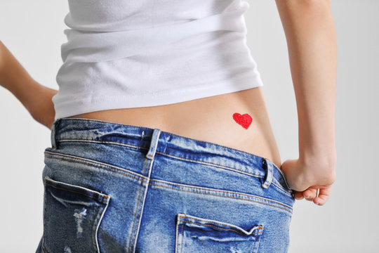 Drawing red heart on female back isolated on white