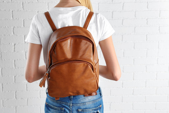 Back of woman with brown leather backpack against white brick wall background