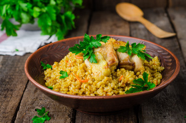 Chicken bulgur pilaf in clay bowl on wooden background. Selective focus