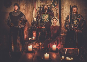 Fototapeta Medieval king with his queen and knights on guard in ancient castle interior. obraz