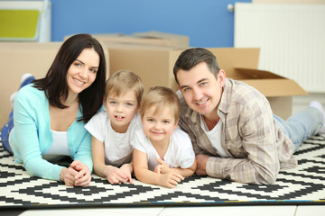 Moving concept. Happy family lying on carpet with cardboard boxes in new house