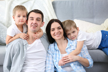 Happy family sitting on floor  on couch background, closeup