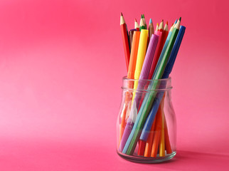 Colorful stationery in glass jar on pink background