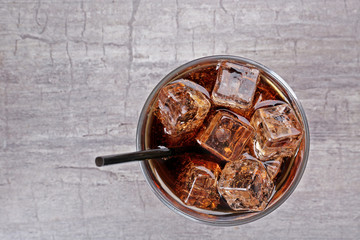 Glass of cola with ice on rustic wooden background