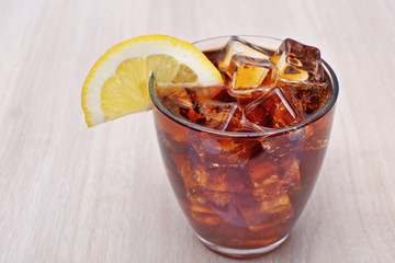 Glass of cola with ice on light wooden background