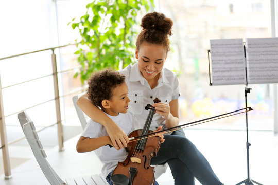 Young girl teaching little boy to playing  violin