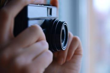 Female hands holding retro camera closeup