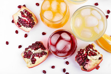 Iced pomegranate and orange drink with fresh fruits isolated on white