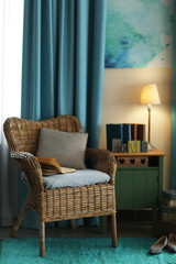 Design interior with wicker armchair and wooden nightstand indoors