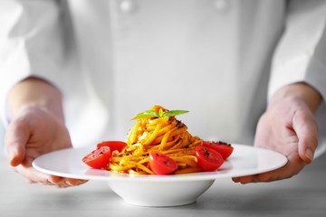 Chef hands holding delicious cold pasta salad in bowl on the table closeup