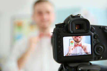 Young male blogger with tie bow on camera screen