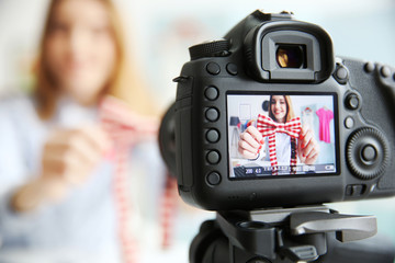Young female blogger with tie bow on camera screen