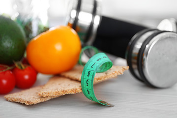 Set of fresh fruits and vegetables with dumbbells on wooden table closeup