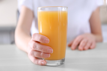 Female hand holding glass of orange juice on wooden table closeup