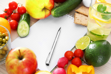 Blank notebook and fresh healthy products on wooden table, closeup