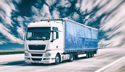 Transport von Gütern mit LKW - fahrender Lastkraftwagen auf der Autobahn // shipping