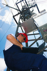 Electrician in red helmet working on electric power pole