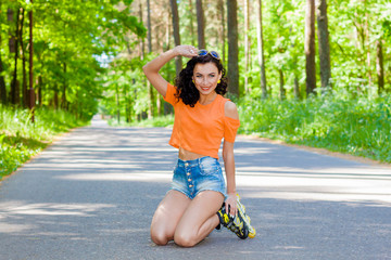 Portrait of positive crazy cheerful girl on roller skates. Young woman in roller skates. happy young brunette woman rides on roller skates in the park and falls