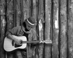 Musician playing guitar leaning timber wall. Black and white photo.