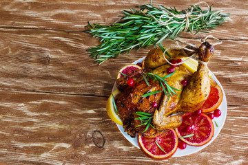 Roasted whole chicken on wooden table. Served with red oranges, lemon, rosemary and cranberries. Top view.