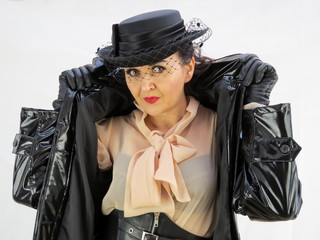 Woman in black PVC mac wearing a hat