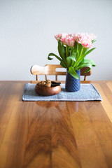 Tulips in blue vase and nuts in wooden bowl on wooden table. Selective focus.