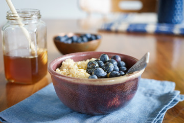 Oats porridge served with blueberries and honey. Selective focus.