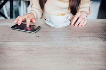 Woman using mobile phone in a cafe