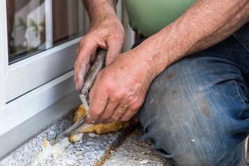 Arbeiterhände - Handwerker entfernt mit einer Spachtel PU Schaum