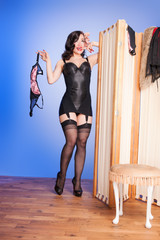 Kitsch retro boudoir girl in black lingerie & stockings preparin