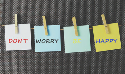 "Life inspiration quotes ""don't worry, be happy"" on colorful paper attached on a string with clothes pin"