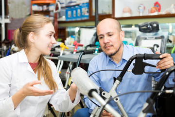 Female consultant offering wheelchair to mature customer