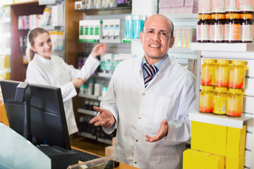 Friendly professional pharmaceutists at reception of drugstore
