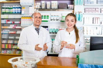 Friendly positive pharmaceutists at reception of drugstore